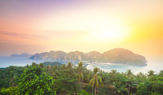 Spectacular landscape the limestone cliffs in the crystal clear ocean next to the exotic phi phi islands, the kingdom of thailand. amazing sunrise in golden shades.