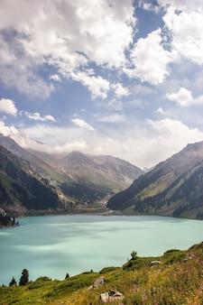 카자흐스탄 알마티 지역의 티엔-샨 산맥(tien-shan mountains), 빅 알마티 호수(big almaty lake)의 장엄한 경치. 수직의.