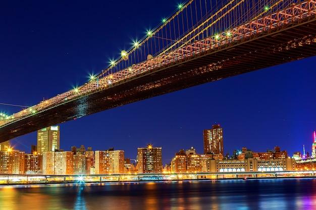 Захватывающий горизонт центра манхэттена, включая бруклинский мост бруклинский мост в нью-йорке ночью