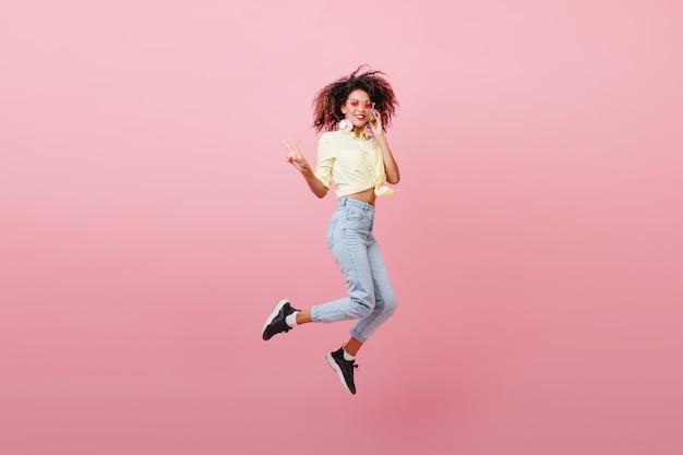 幸せそうな顔で踊る茶色の肌を持つ壮大なスポーティな女性。ポジティブな感情を表現する黒いスニーカーの愛らしいムラートの女の子。