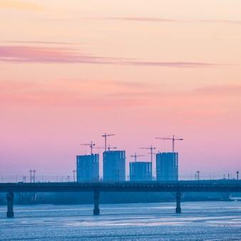 ドニエプル川に架かる橋のある壮大な夕日の街の景色。キエフ、ウクライナ