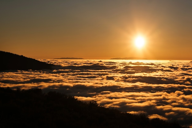 A spectacular sunset above the clouds in the national park of the volcano teide on tenerife. excellent sunset in the canary islands.