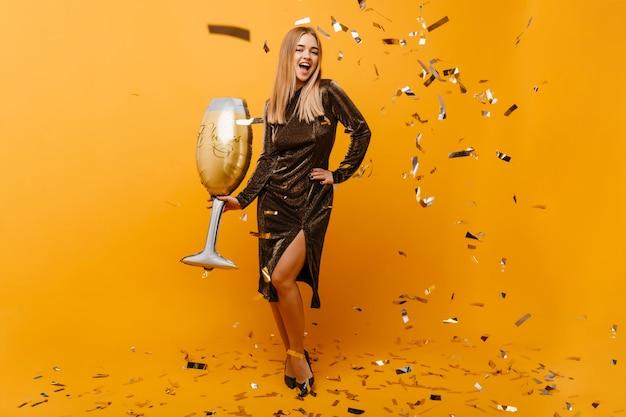 장난감 와인 글라스와 함께 포즈를 취하는 화려한 키 큰 여자. 오렌지에 춤 파티 드레스에 blinde 여자를 웃 고있다.