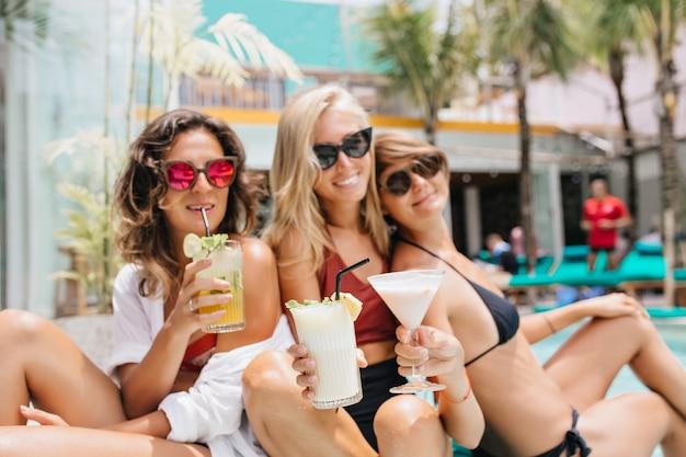 여름 주말에 수영장에서 함께 포즈를 취하는 비키니 입은 멋진 무두질 여성. 이국적인 리조트에서 휴식하는 동안 칵테일을 마시는 세 여성 모델의 야외 촬영.