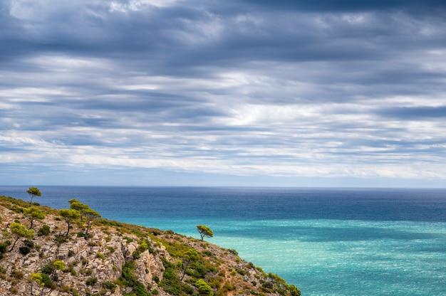 Захватывающий вид на скалу и море с пасмурным небом.