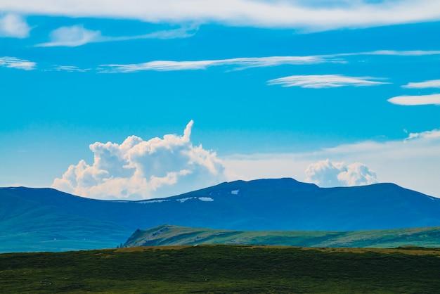 Захватывающий вид на гигантские горы со снегом. огромное облако над горой. большой скалистый утес над пропастью. прекрасные дикие пейзажи. атмосферный горный ландшафт величественной природы. живописный горный пейзаж.