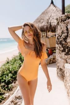 シーリゾートで身も凍るように、バンガローの近くでポーズをとる壮大な白人女性モデル。オレンジ色の水着を着た優雅なスリムな女性が黒髪にふざけて触れている屋外ショット。