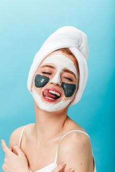 スキンケア治療中に楽しんでいる壮観な女性。青い背景にポーズをとるフェイスマスクを持つ魅力的な女の子のスタジオショット。