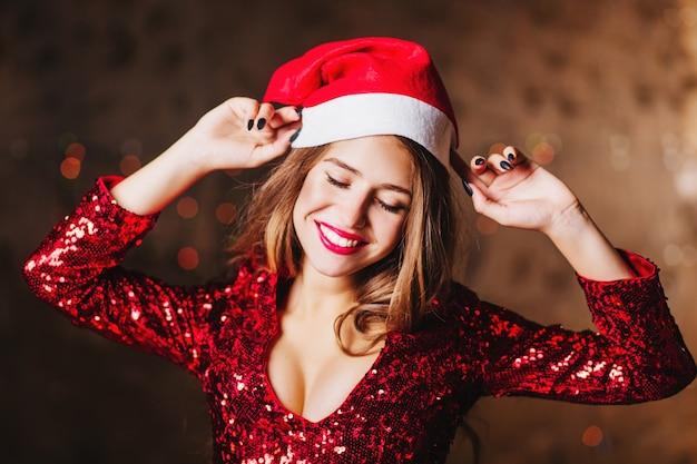 Эффектная женщина в красном блестящем платье танцует на рождественской вечеринке