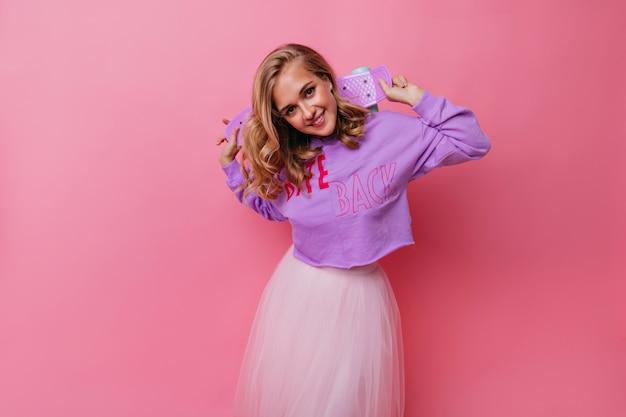 スケートボードを保持しているトレンディな紫色のシャツの壮大な女性。恍惚とした巻き毛のブロンドの女の子の屋内肖像画