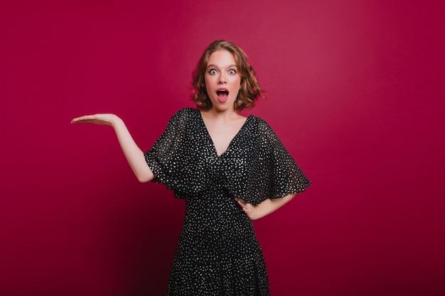 Spettacolare donna in sciarpa lavorata a maglia alla moda che copre gli occhi con le mani. foto interna di una donna accattivante che ride in cappello e maglione in posa divertente davanti al muro viola