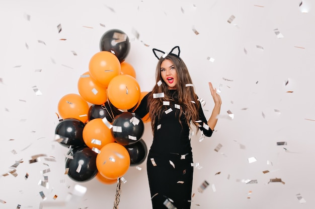 Spectacular woman with long hair standing under confetti with surprised smile
