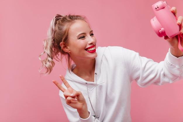 Spettacolare donna con i capelli biondi lucidi utilizzando la parte anteriore per selfie