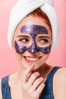 Spectacular young woman doing spa treatment with sincere smile. studio shot of glad girl with face mask and towel.