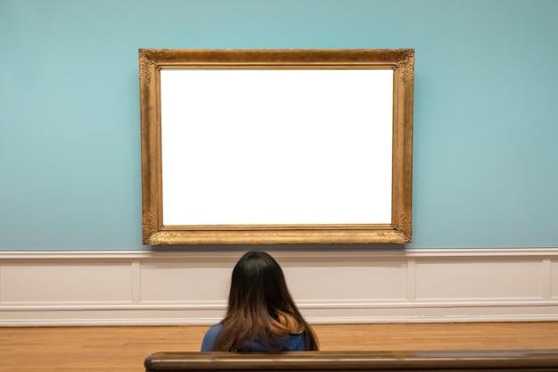 미술관의 파란색 벽에 빈 대형 금색 프레임을 보고 있는 관객