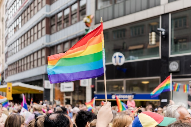 A spectator waves a gay rainbow flag flying on sidelines of a summer gay pride parade
