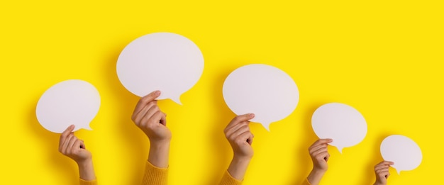 Speech bubbles in hand over yellow background, panoramic layout over dialogue icon
