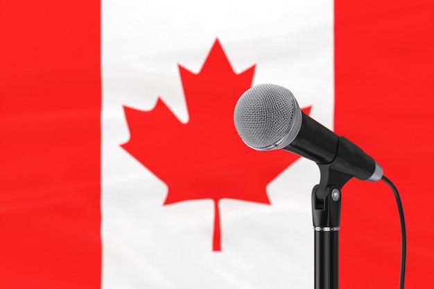 ぼやけたカナダ国旗の極端なクローズアップに対するスピーチマイクスタンド。 3dレンダリング