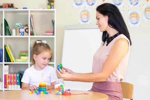 언어 치료사는 소녀를 가르칩니다. 어린이 피라미드, 아동 발달, 미세 운동 기술 수집