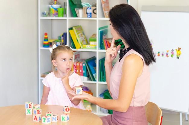 언어 치료사는 소녀에게 말하기를 가르칩니다.