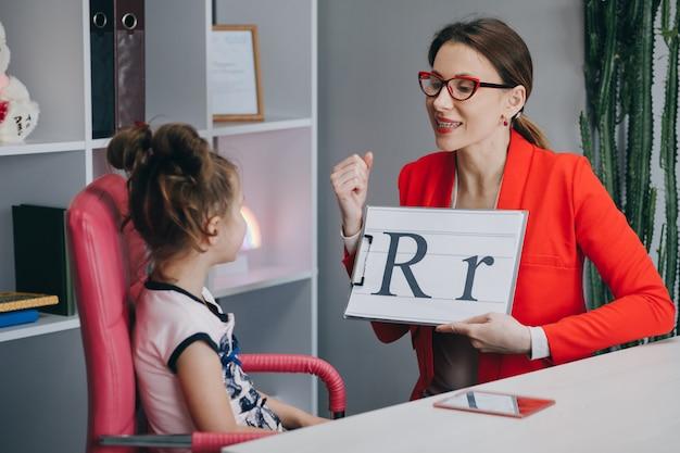 언어 치료사는 소녀들에게 편지 r을 말하도록 지시합니다.