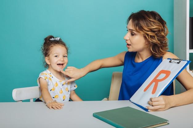 언어 치료 개념. 함께 편지를 배우는 치료사와 아이.