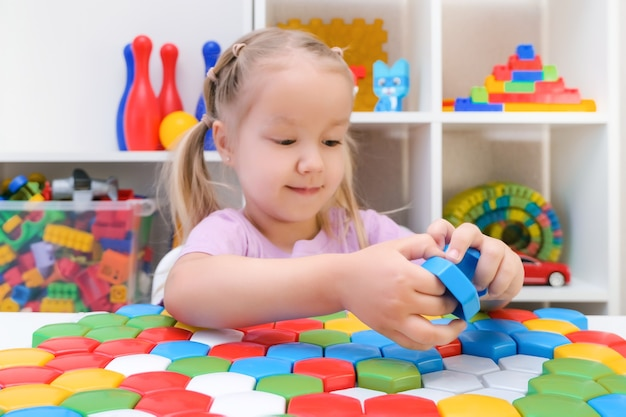 Speech therapy, the development of fine motor skills. girl playing puzzle, happy child