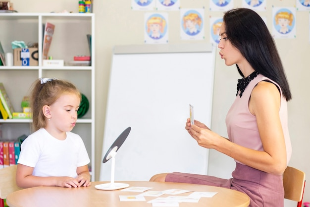 Speech therapy exercises and games with a mirror and cards