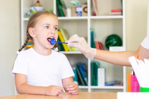 少女の舌の言語療法マッサージ。言語聴覚士は、ステージングプローブを使って子供に舌マッサージをします。