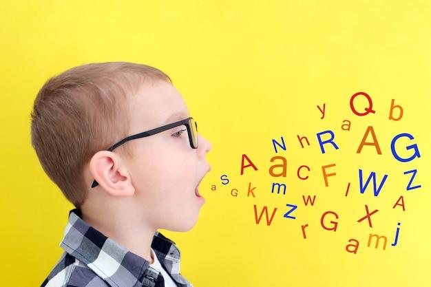 言語療法。幼児の男の子は文字で口を開けると言います。言語聴覚士による授業。孤立した黄色の背景の少年