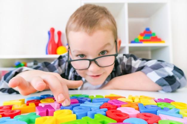 言語療法。文字を持つ幼児の男の子。言語聴覚士による授業。