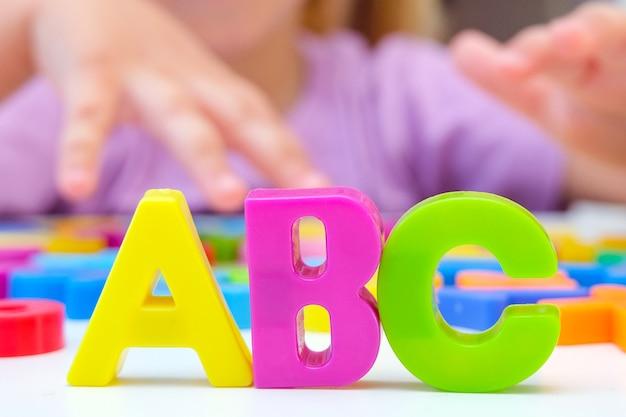 言語療法。文字と幼児の女の子。言語聴覚士による授業。 abc