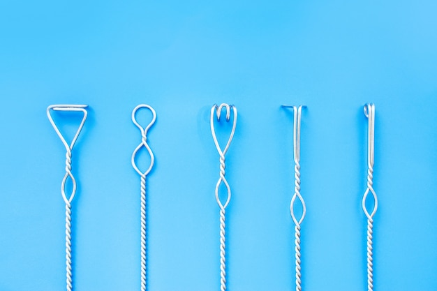 Speech therapy tools on a blue background. logopedic metal probes. speech correction