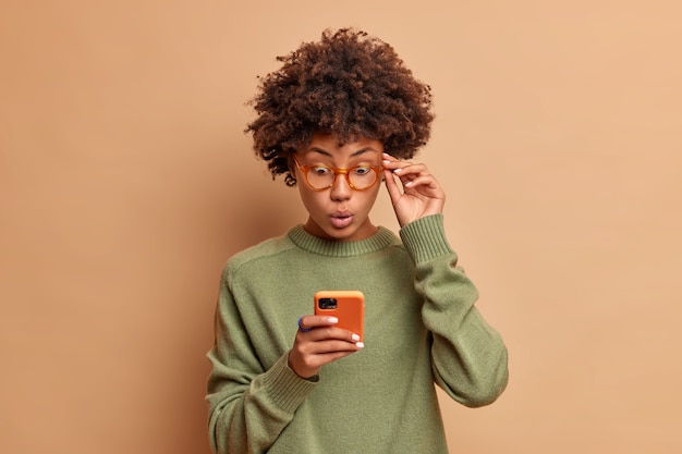 Speechless impressed curly beautiful woman stares at smartphone stands with bugged eyes keeps hand on rim of spectacles wears casual jumper has shocked expression reads news