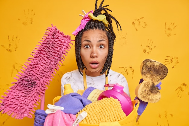 言葉のない印象的な暗い肌の女性は、omg式で三つ編みの凝視を梳きましたすべてをきれいにします汚れた洗浄装置は黄色の壁の上に隔離された洗浄を行います