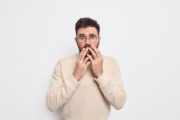 Безмолвный испуганный мужчина смотрит с испугом, дрожит от страха, держит руки во рту, носит круглые очки и джемпер