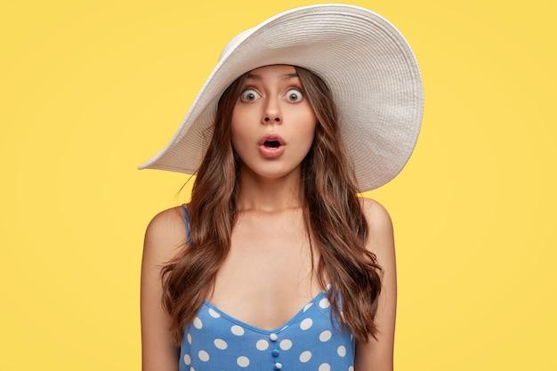 Una donna sconvolta senza parole nota qualcosa di terribile e orribile, indossa un cappello da spiaggia bianco, un vestito blu, tiene la mascella a bocca aperta dalla paura, isolata su un muro giallo, spalanca gli occhi con stupore.