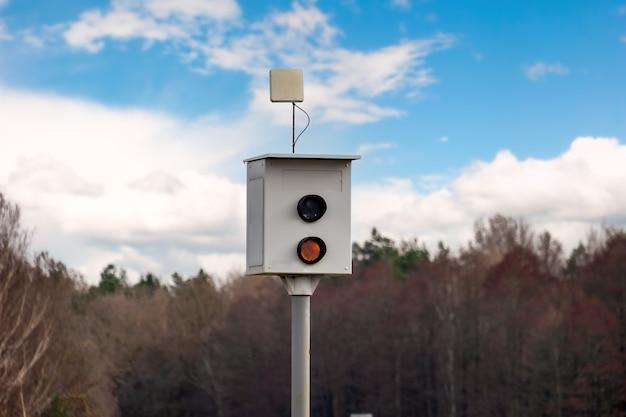 지나가는 차량의 속도를 측정하기 위한 과속 카메라는 시골길에 서 있습니다.