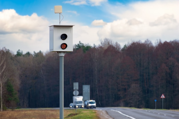 Speed camera for measuring speed of passing vehicles stands at countryside road. radar installed on roadside to control speed limit.