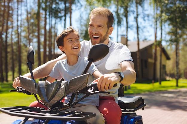 スピードドライブ。息子と一緒に笑顔で全地形対応車を運転するインスピレーションを得た若い父親