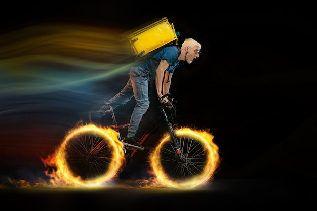 スピード。迅速な配達サービス-暗い背景に火がついた状態で自転車を運転している配達員。広告のコピースペース。検疫中の食品および商品の注文の超高速配送。