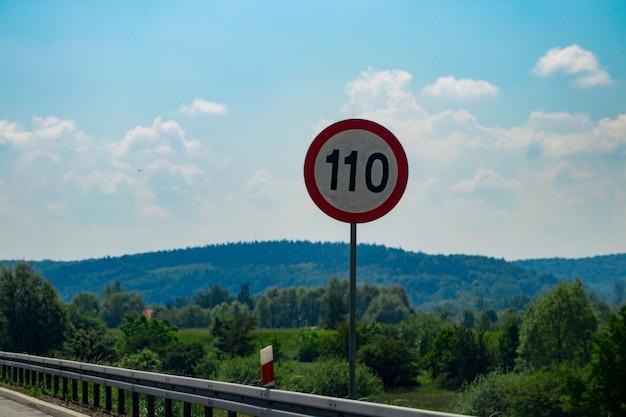 青い空を背景に制限速度標識。