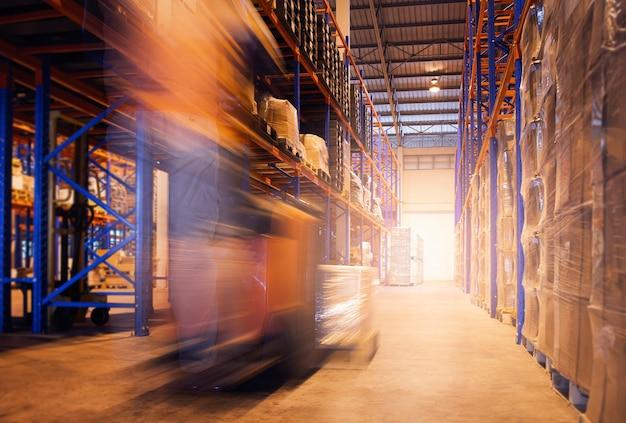 Скорость размытость изображения водителя погрузчика, разгружающего коробки с упаковками на складе