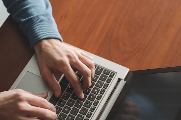 スピードタイピングトレーニング。男はノートパソコンのキーボードを手渡します。オフィススキルの向上
