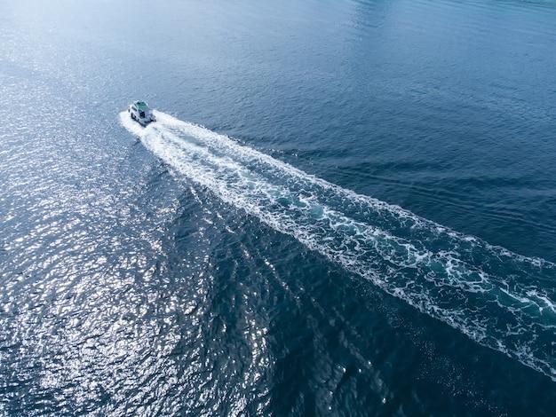 Скоростной катер плывет по синему морю навстречу солнцу. отдых для туристов и купание в море.
