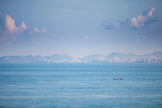 Speedboats sail the industrial coast.