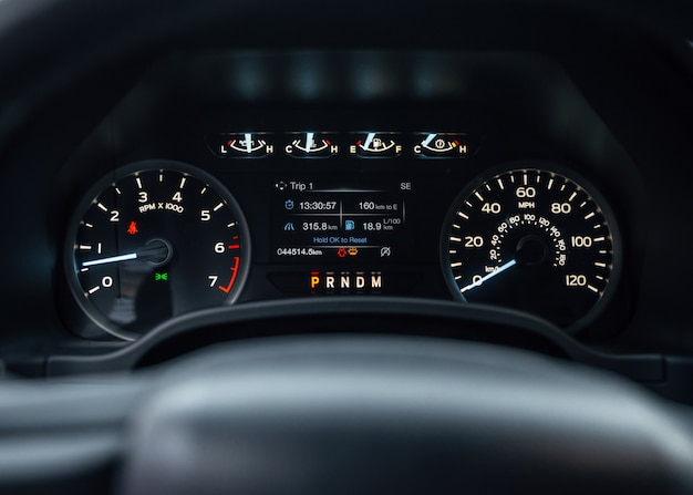 Speedometer of modern car with integrated fuel gauge in tank starting engine with warning lights on