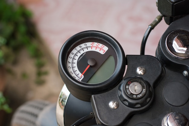 Speedometer on motorcycle dashboard. round speedometer with red arrow. speed zero shown.