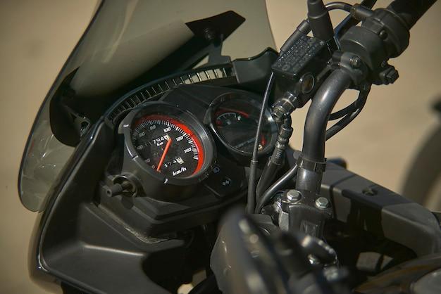 現代のエンデューロバイクのスピードメーター、ハンドルバーとよく見えるブレーキポンプを備えたインストルメントクラスターの詳細。 Premium写真