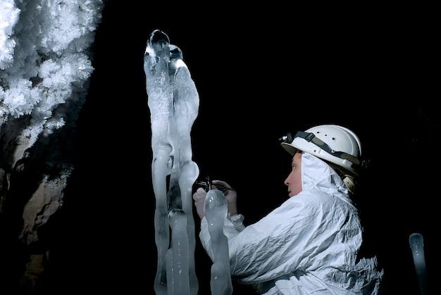 동굴학자는 어둠의 배경에서 얼음 구조의 샘플을 가져옵니다.
